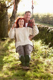 Couple on swing in country garden. Smiling Royalty Free Stock Images