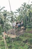 Couple swings in the deep jungle of Bali island. Indonesia Royalty Free Stock Photo