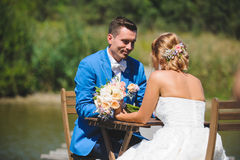 Couple at Table with Bouquet. Couple sitting at woorden table on bridge Stock Photography