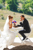 Couple at Table. Bride and groom sitting at table outdoors Stock Photos
