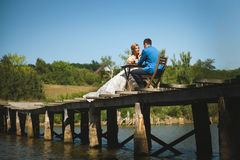 Couple at Table on Bridge. Bride and groom sitting at table on wooden bridge Royalty Free Stock Photo