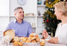 Couple at the table celebrating Christmas and New Year at home. Positive spanish mature couple at the table celebrating Christmas and New Year at home royalty free stock photography