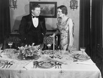 Couple with table set for dinner Royalty Free Stock Photo