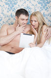Couple with tablet computer in bed Stock Image