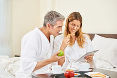 Couple with tablet computer having breakfast Royalty Free Stock Photography