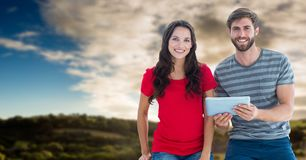 Couple with tablet with flare against sky and hills Stock Photography