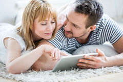Couple with tablet lying on floor and surfing the net Royalty Free Stock Image