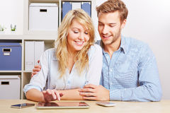 Couple with tablet PC. Couple playing around with a tablet PC and some smartphones in the living room Royalty Free Stock Photography