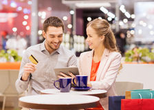 Couple with tablet pc and credit card in mall. Sale, shopping, consumerism, leisure and people concept - happy couple with tablet pc and credit card drinking Stock Photo