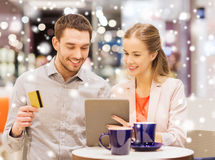 Couple with tablet pc and credit card in mall. Sale, shopping, consumerism, leisure and people concept - happy couple with tablet pc and credit card drinking Stock Photos