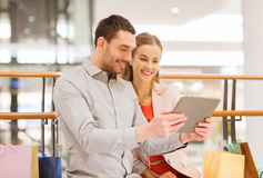 Couple with tablet pc and shopping bags in mall Royalty Free Stock Photos