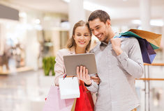 Couple with tablet pc and shopping bags in mall. Sale, consumerism, technology and people concept - happy young couple with shopping bags and tablet pc computer Royalty Free Stock Photo