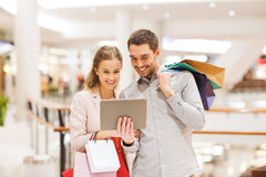 Couple with tablet pc and shopping bags in mall Royalty Free Stock Photography