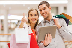 Couple with tablet pc and shopping bags in mall. Sale, consumerism, technology and people concept - happy young couple with shopping bags and tablet pc computer Royalty Free Stock Image