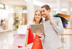 Couple with tablet pc and shopping bags in mall. Sale, consumerism, technology and people concept - happy young couple with shopping bags and tablet pc computer royalty free stock photos