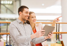 Couple with tablet pc and shopping bags in mall Royalty Free Stock Images