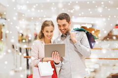 Couple with tablet pc and shopping bags in mall. Sale, consumerism, technology and people concept - happy young couple with shopping bags and tablet pc computer Royalty Free Stock Images