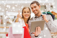 Couple with tablet pc and shopping bags in mall. Sale, consumerism, technology and people concept - happy young couple with shopping bags and tablet pc computer Stock Image