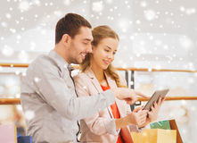 Couple with tablet pc and shopping bags in mall. Sale, consumerism, technology and people concept - happy young couple with shopping bags and tablet pc computer Stock Photo