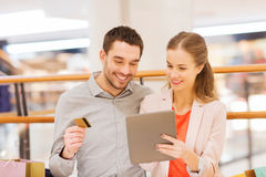 Couple with tablet pc and shopping bags in mall Stock Photo