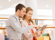 Couple with tablet pc and shopping bags in mall Stock Images