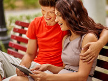 Couple with tablet pc sit on bench Royalty Free Stock Image