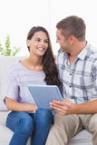 Couple with tablet PC sitting on sofa Royalty Free Stock Images