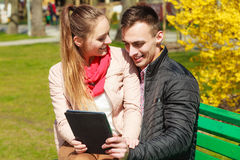 Couple with tablet sitting on bench outdoor Royalty Free Stock Images