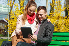 Couple with tablet sitting on bench outdoor Royalty Free Stock Photos