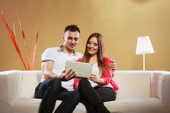Couple with tablet sitting on couch at home Stock Image