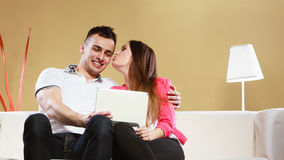 Couple with tablet sitting on couch at home Royalty Free Stock Photography