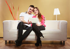 Couple with tablet sitting on couch at home Royalty Free Stock Image