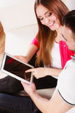 Couple with tablet sitting on couch at home Stock Images