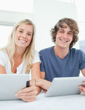 A couple with tablets smile and look at the camera Stock Images