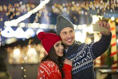 Couple take selfie at Christmas market. Young Couple Having Fun Outdoors At Christmas Time, Europe royalty free stock photos
