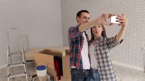 The couple takes a selfie in the new apartment. A young happy couple taking a selfie in their new apartment in the background is worth a lot of cardboard boxes stock footage