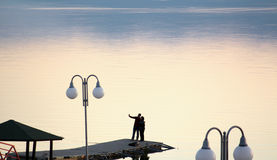 Couple takes selfy on a pier on a lake prespa in macedonia.sunset over lake . Royalty Free Stock Photo