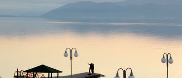Couple takes selfy on a pier on a lake prespa in macedonia.sunset over lake . Royalty Free Stock Photos