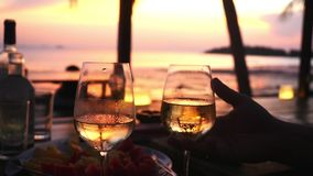 Couple takes two glasses in their hands with white wine against the sunset at the sea. slow motion, 1920x1080 stock video footage