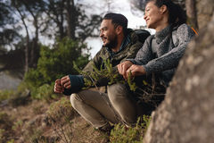Couple taking a break after hiking uphill in the countryside. Young men and women sitting on mountain and looking away Royalty Free Stock Photo