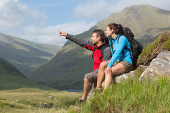Couple taking a break after hiking uphill with man pointing Stock Photo