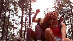 Couple taking a break after hiking uphill. In slow motion stock video