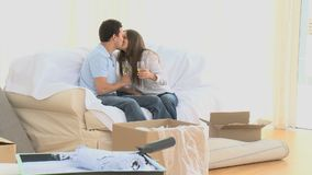 Couple taking a break during the move with a glass of white wine. Couple taking a break during the move with glass of white wine sitting on the sofa stock footage