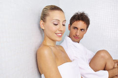 Couple taking a break after sauna session. Smiling couple taking a break after sauna session in relaxation room stock photography