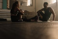 Couple taking break after training session at gym royalty free stock photos