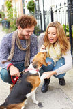 Couple Taking Dog For Walk On City Street Royalty Free Stock Photography