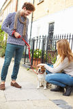 Couple Taking Dog For Walk On City Street Royalty Free Stock Images