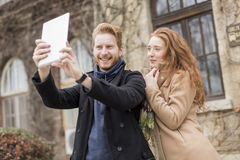 Couple taking photo with tablet Royalty Free Stock Image