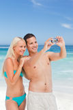 Couple taking a photo of themselves on the beach Stock Images