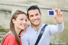 Couple taking photo themselves with digital camera Stock Photo